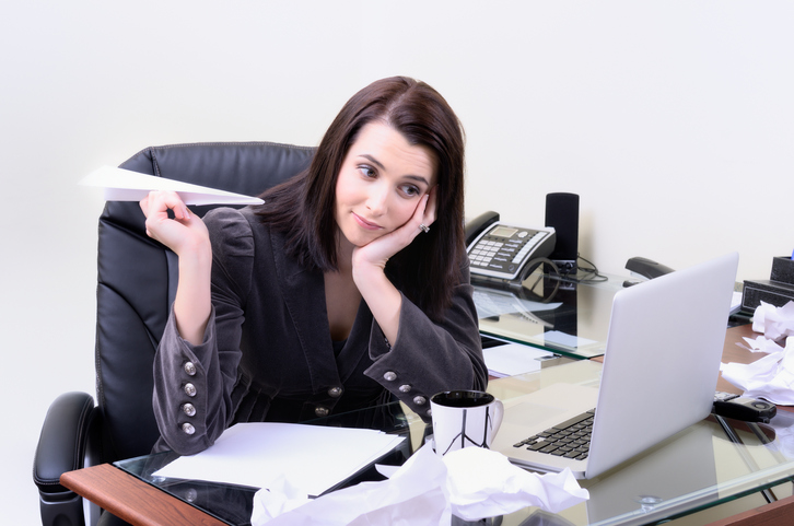 Businesswoman sitting at desk, holding paper plane